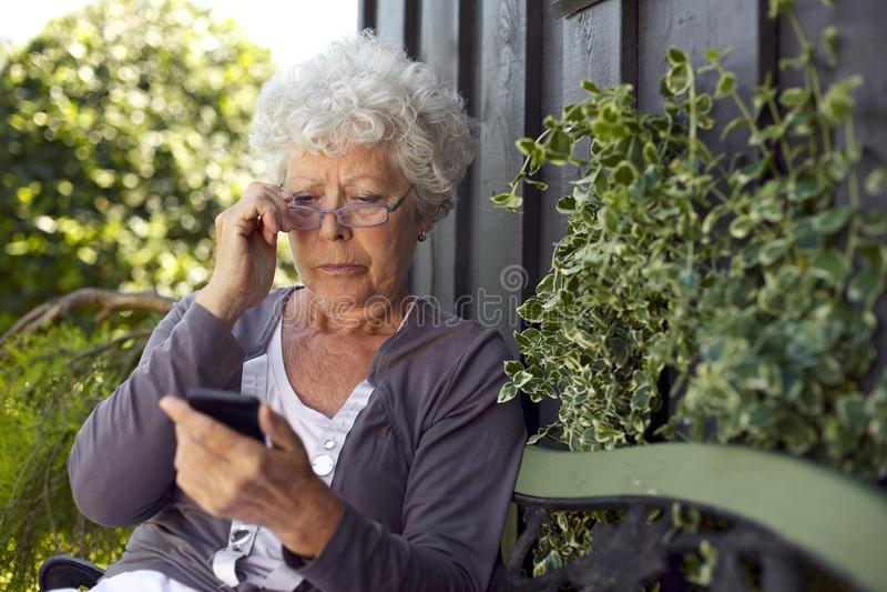 Senior woman looking at mobile phone royalty free stock photos