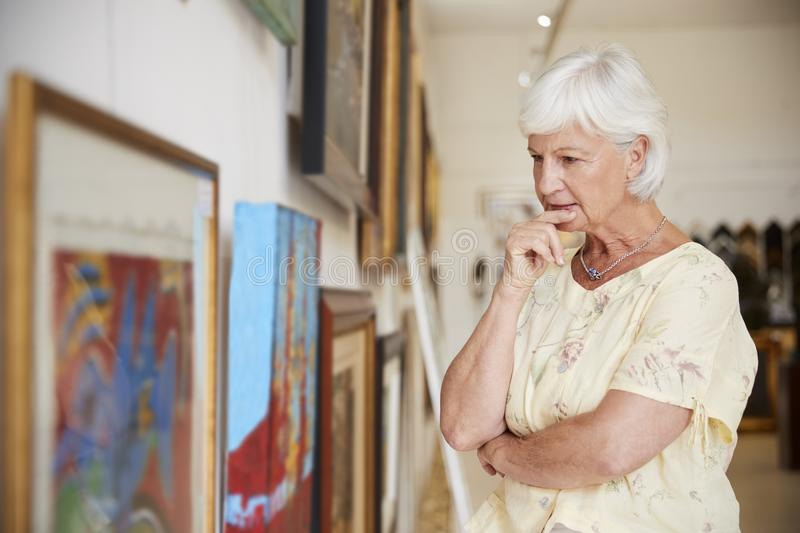 Senior Woman Looking At Paintings In Art Gallery royalty free stock photography