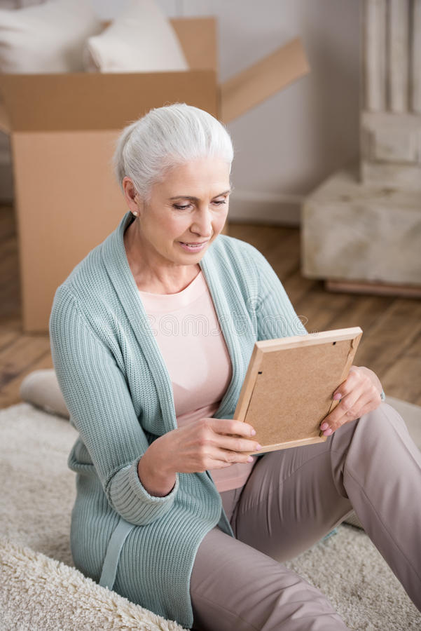 Senior woman looking at photo frame in hands stock photography