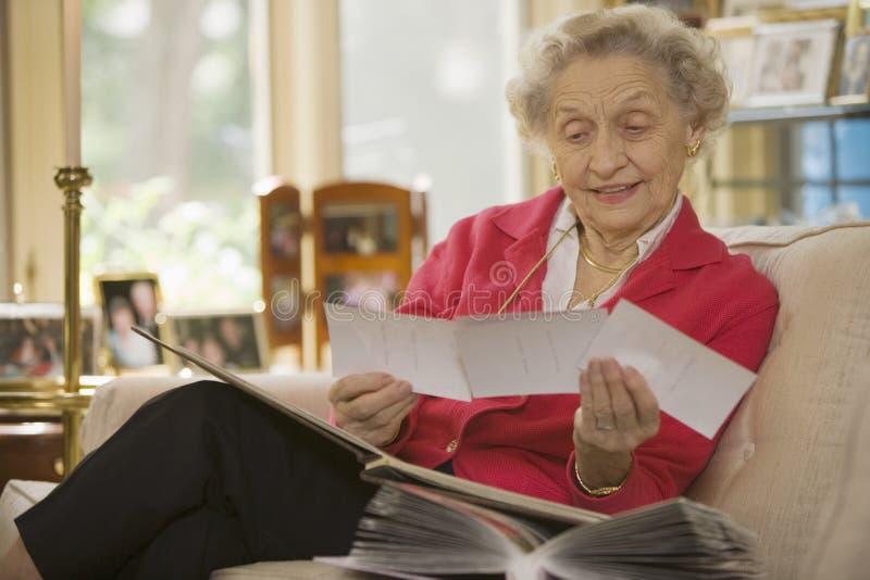 Senior woman looking at photographs. Happy senior woman at home holding a group of photos stock image