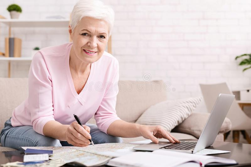 Senior woman looking planning travel with map royalty free stock photo