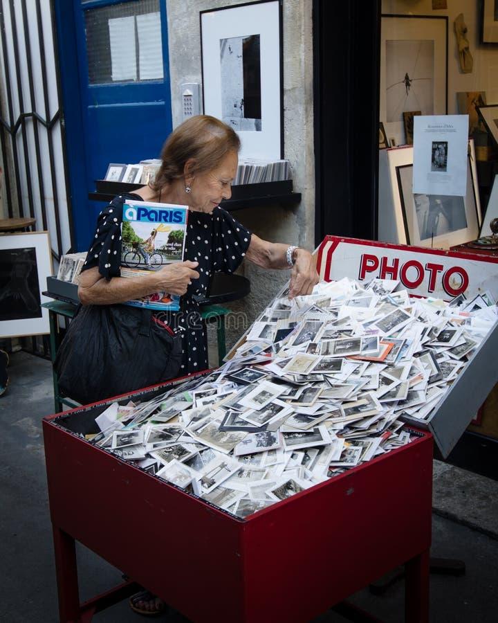 Senior woman looks through a box of old photos at an outdoor market. PARIS, FRANCE AUGUST 29, 2015 Senior woman looks through a box of old black and white photos stock photography