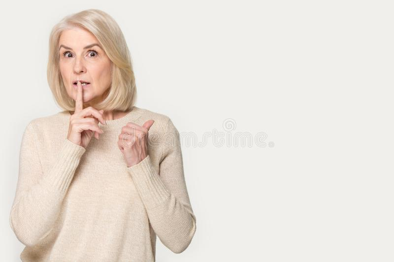 Senior woman makes hush sign pointing finger aside at copyspace royalty free stock photo