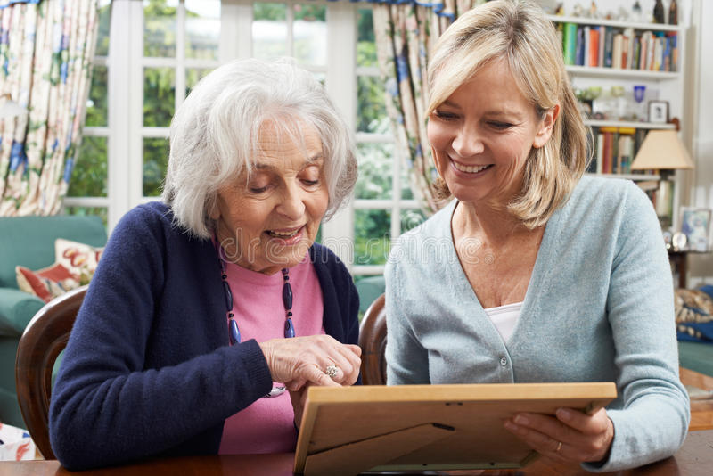Senior Woman Looks At Photo Frame With Mature Female Neighbor royalty free stock image