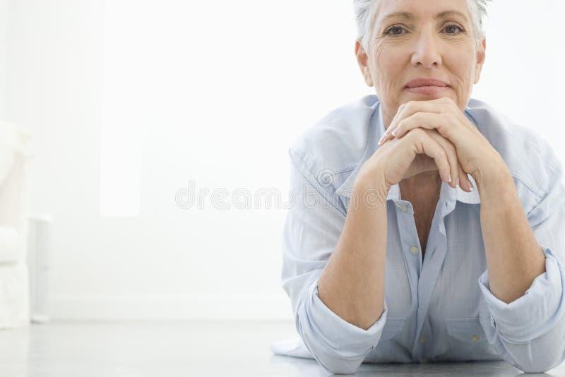 Senior Woman Lying On Floor royalty free stock image