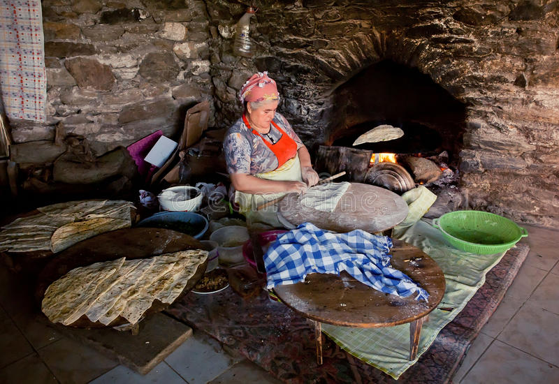 Senior woman making pastry for traditional food Gozleme inside rustic kitchen of old turkish village stock images