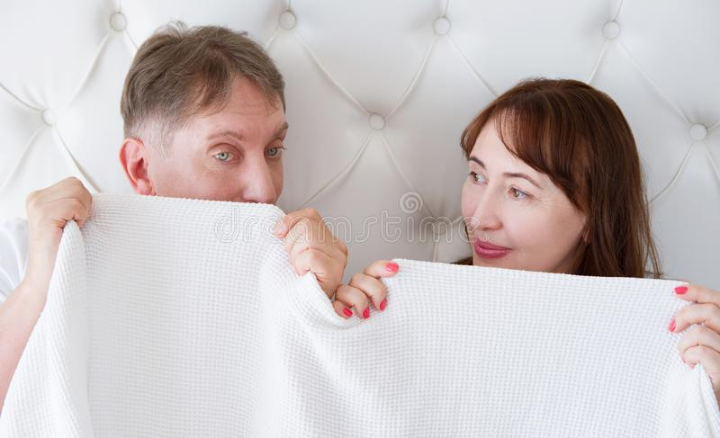 Senior Woman and man in bed. Middle age couple lying in bedroom and hiding under template blank white blanket. Copy space. Banner. Senior Woman and men in bed stock photo