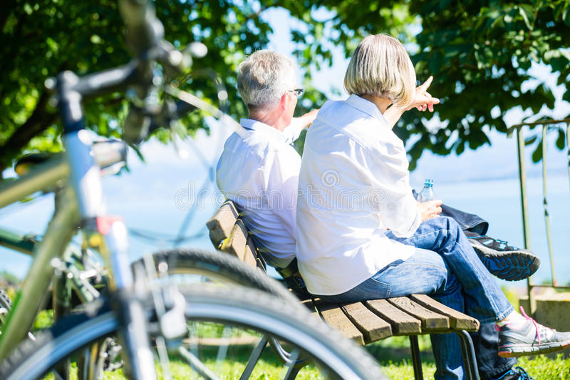 Senior woman and man at rest on bike trip stock image