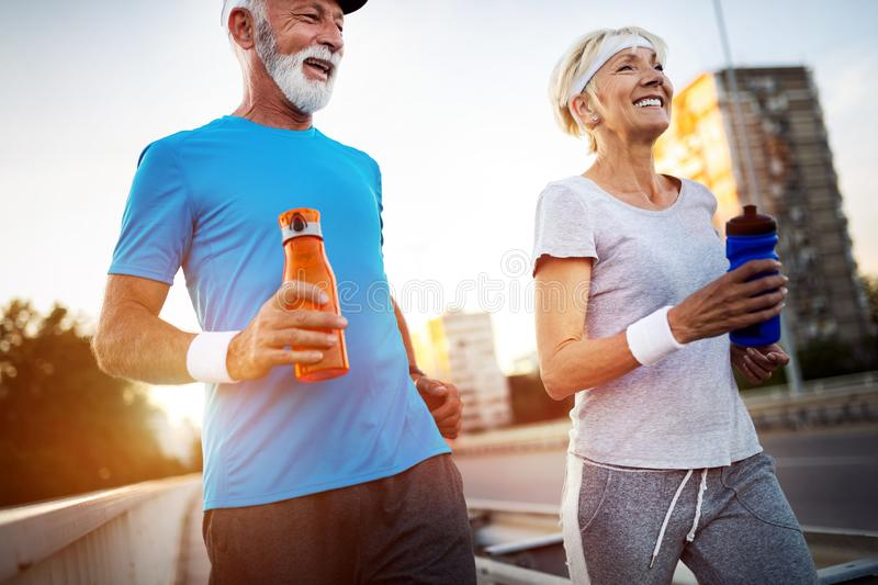 Senior woman and man running doing fitness exercises royalty free stock photos