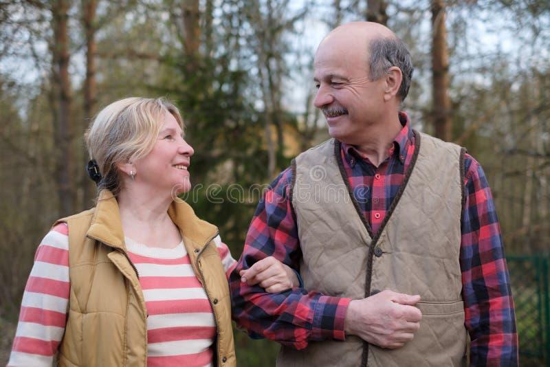 Happy elderly senior couple cycling in park stock photos