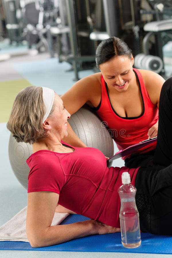Senior woman on mat with personal trainer stock image