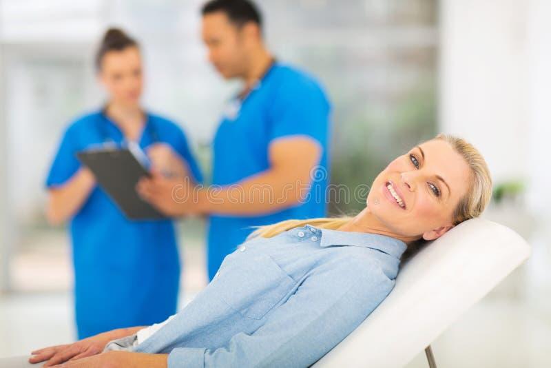 Senior woman medical checkup. Happy senior women lying on doctor's examining bed and waiting for medical checkup stock image