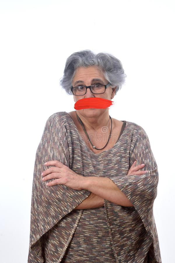 Senior woman with mouth covered on white royalty free stock image