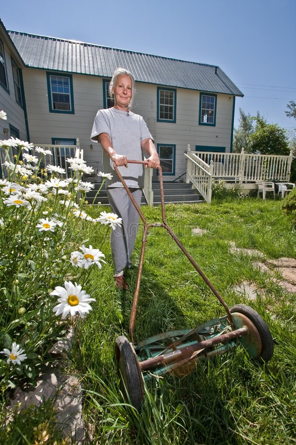 Low Angle View Of A Senior Woman Mowing A Lawn High-Res