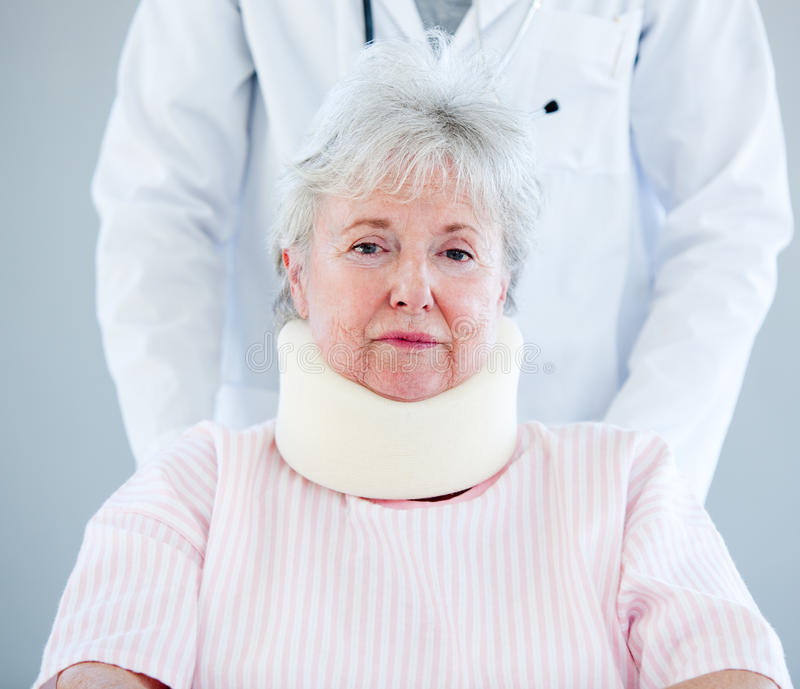 Senior woman with a neck brace sitting on a wheelc. Portrait of a senior woman with a neck brace sitting on a wheelchair in a hospital stock photography