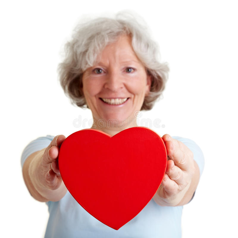 Senior woman offering red heart royalty free stock photography