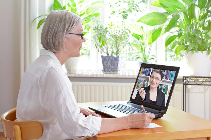 Senior woman online tax advice. Senior women at home in front of her laptop making notes during watching an online video of tax advice by a female accountant stock photos