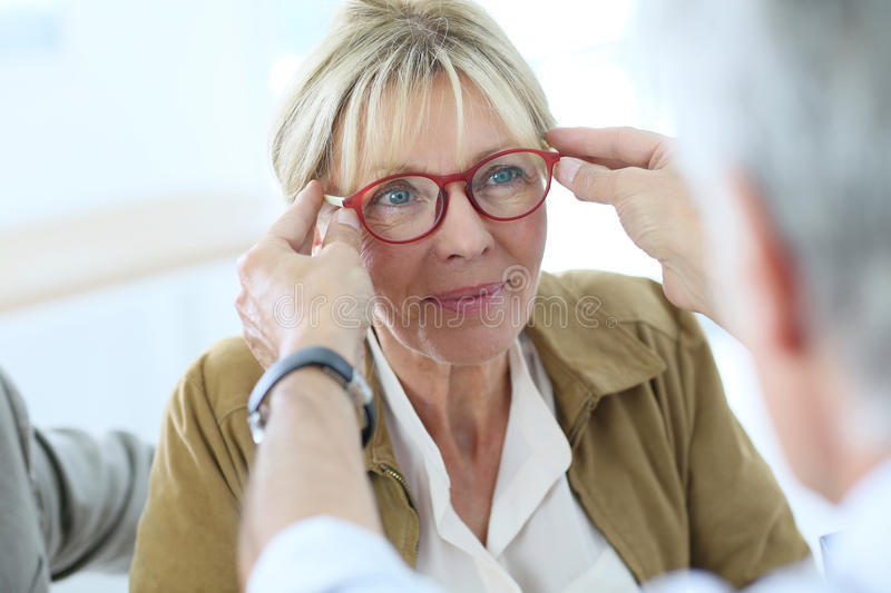 Senior woman in optical store stock photos
