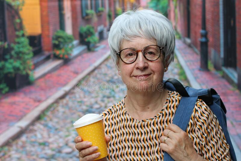 Senior woman outdoors holding coffee cup royalty free stock photos