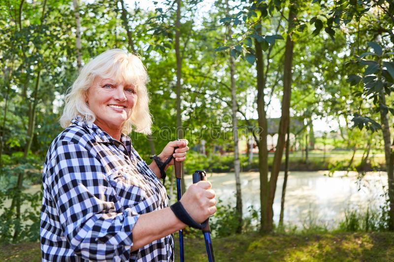 Senior woman with overweight trains endurance. Vital senior woman with overweight trains endurance in Nordic Walking stock photos