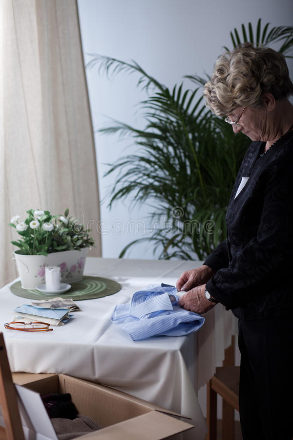 Senior woman packing husband's clothes stock photography