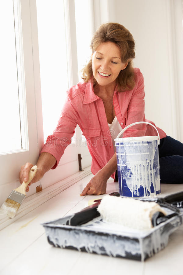 Senior woman painting house stock photography