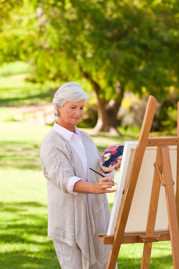 Senior woman painting in the park royalty free stock photography