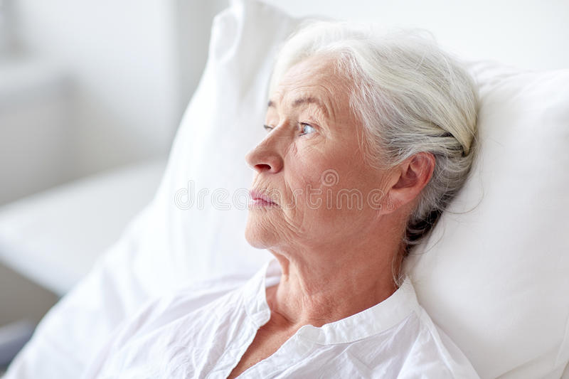 Senior woman patient lying in bed at hospital ward. Medicine, age, health care and people concept - senior woman patient lying in bed at hospital ward stock image