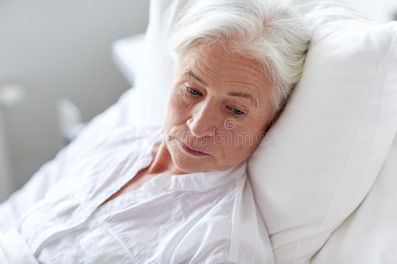 Senior woman patient lying in bed at hospital ward stock photos