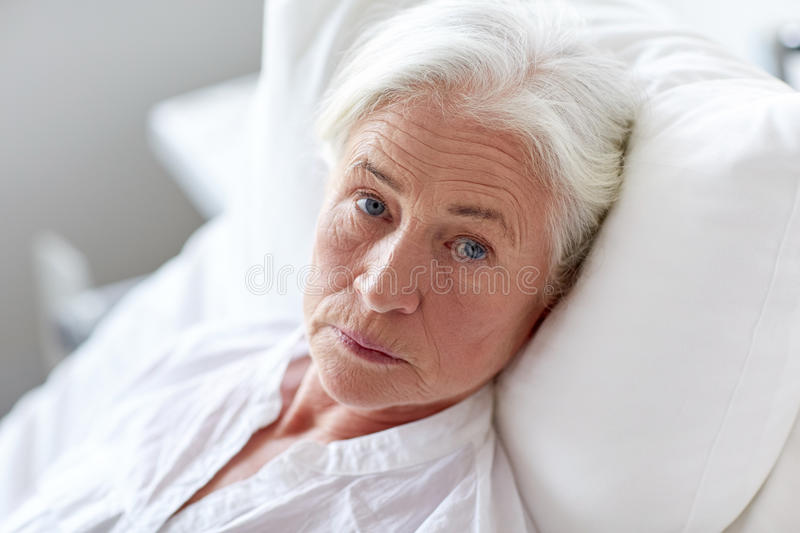 Senior woman patient lying in bed at hospital ward. Medicine, age, health care and people concept - senior woman patient lying in bed at hospital ward stock photography