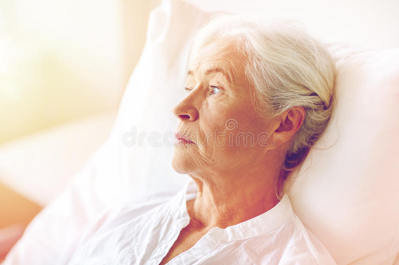 Senior woman patient lying in bed at hospital ward. Medicine, age, health care and people concept - senior woman patient lying in bed at hospital ward royalty free stock image
