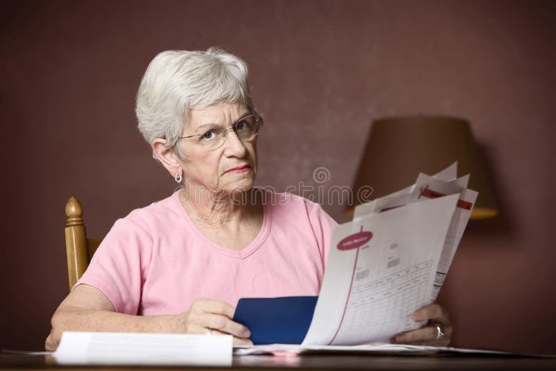 Senior woman paying bills stock photos