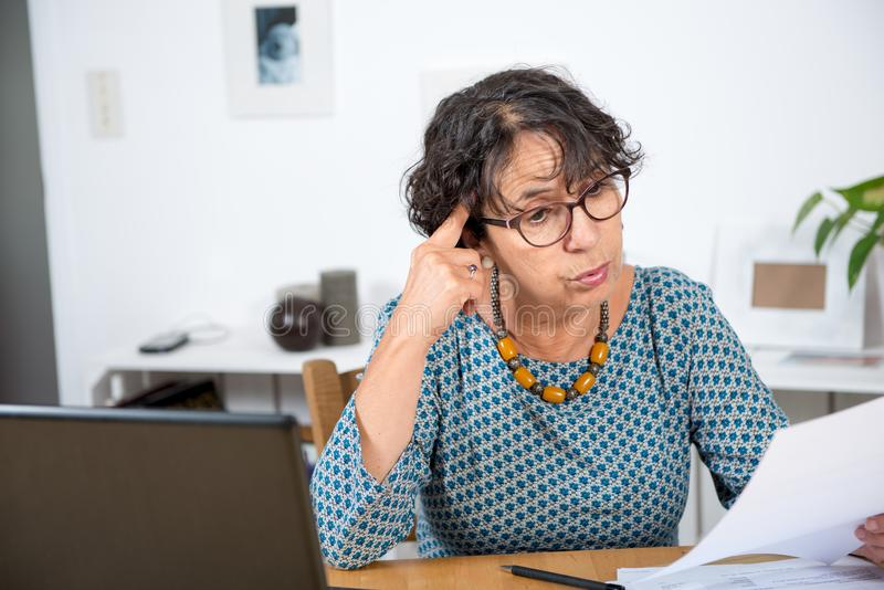 Senior woman paying bills with laptop at home stock photography
