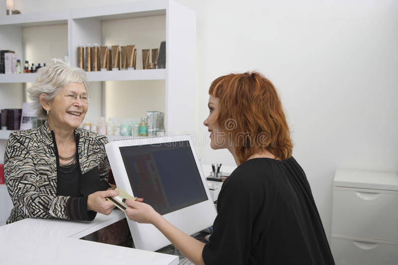 Senior Woman Paying For Her Haircut At Reception Desk. Smiling senior women paying for her haircut through credit card at reception desk royalty free stock photos