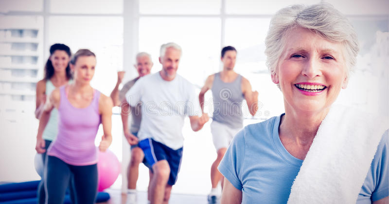 Senior woman with people exercising in fitness studio. Portrait of a cheerful senior women with people exercising in the background at fitness studio royalty free stock photography
