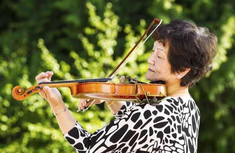 Senior woman performing music outdoors stock photo