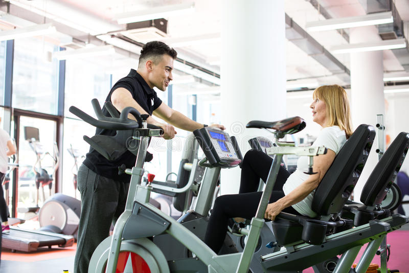 Senior woman with personal trainer at fitness centre royalty free stock image