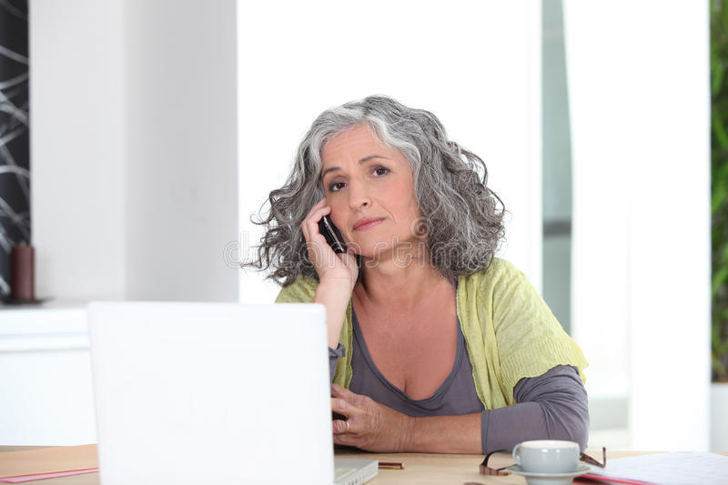 Senior woman on the phone stock images