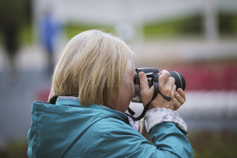 Senior woman with photo camera at summer day in park, outdoor, rear view. Telephoto shot stock photos
