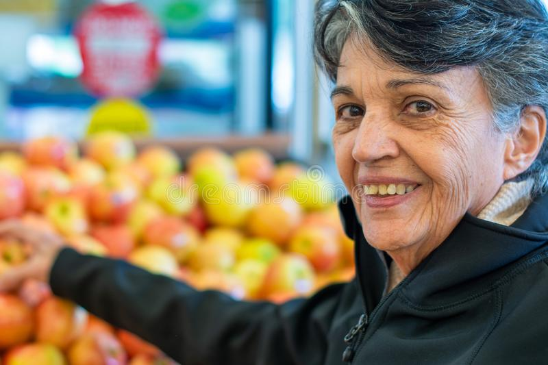 Senior woman picking an apple in a grocery store stock photos