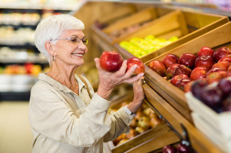Senior woman picking out red apple. In supermarket royalty free stock photography
