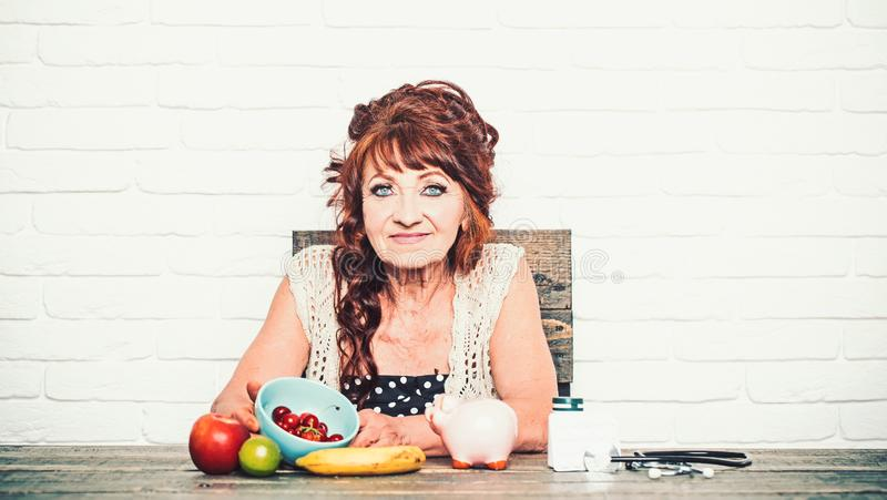 Senior woman with piggy bank, fruit, medicine, stethoscope at table stock images