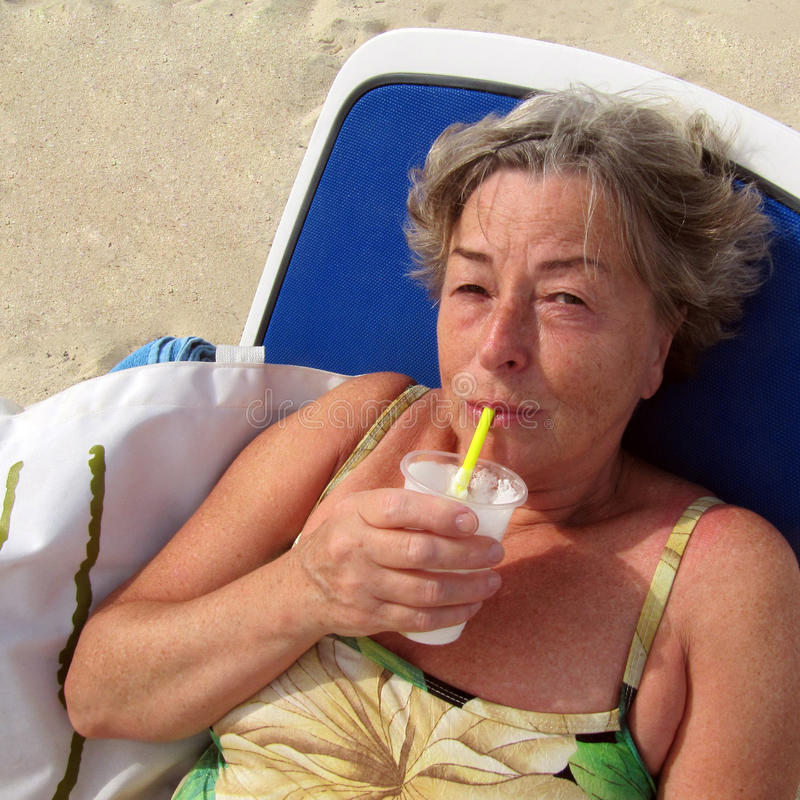 Senior woman with pinacolada royalty free stock photography