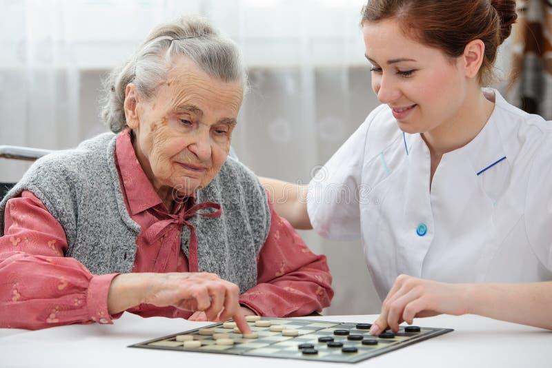 Senior woman playing checkers stock image