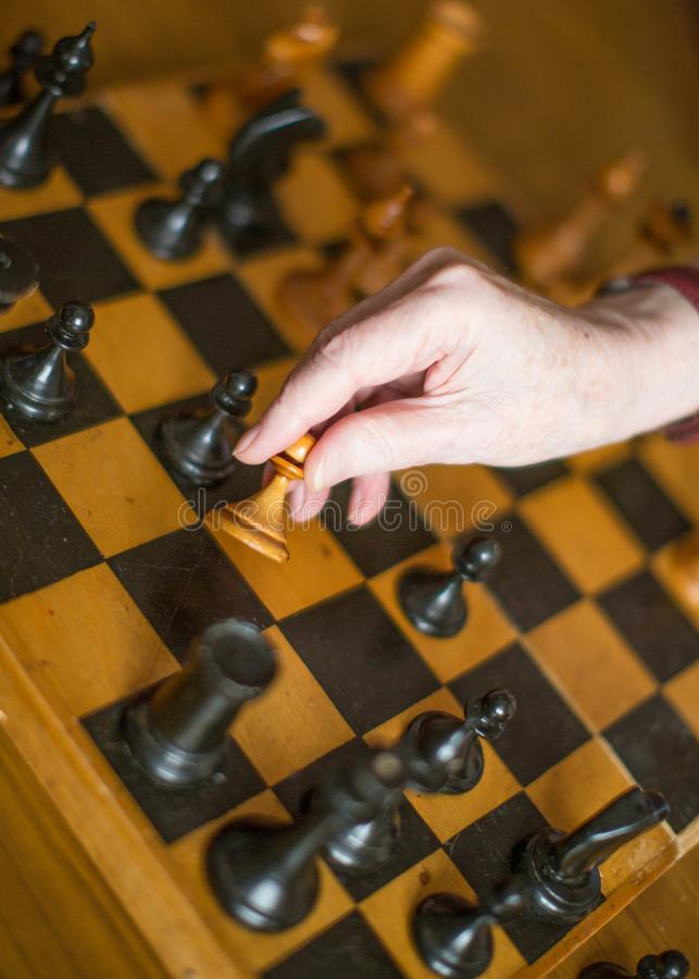 Senior woman playing chess. Close up view of a old female hands with chess stock images