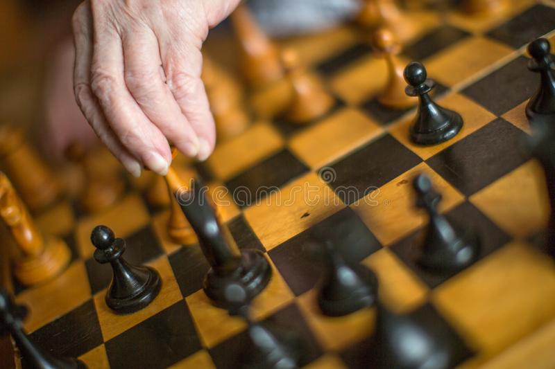 Senior woman playing chess. Close up view of a old female hands with chess royalty free stock photography