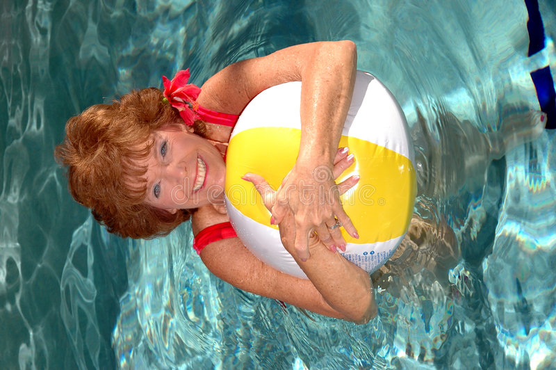 Senior woman in the pool. An attractive smiling senior woman in the pool with a beach ball royalty free stock photography