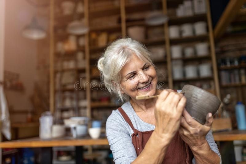 Senior woman pottery artist makes ceramics from clay. Portrait of senior female pottery artist in her art studio royalty free stock photo