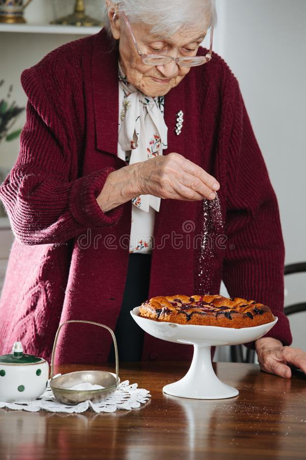 Senior woman pouring powdered sugar on tasty holiday pie on a table stock photos