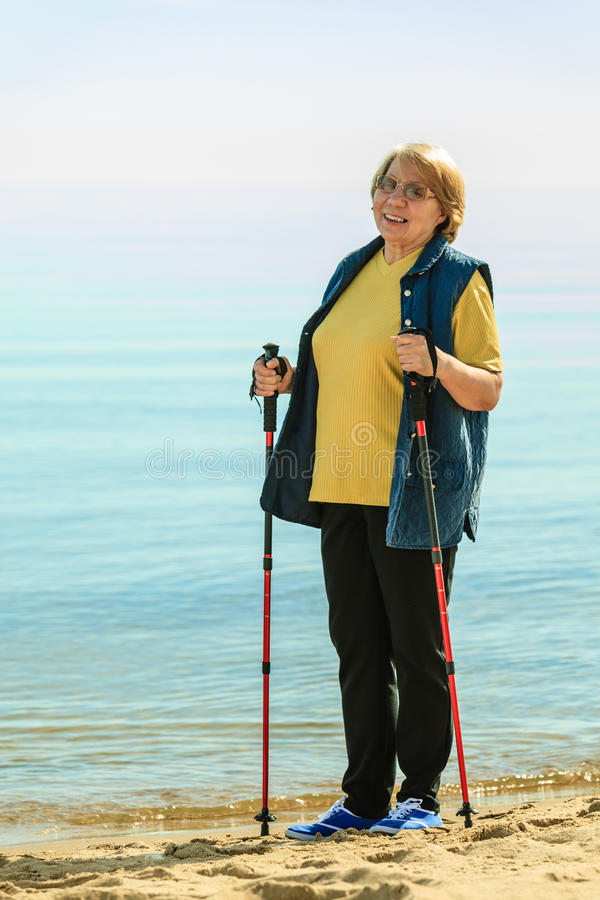 Senior woman practicing nordic walking on beach. Healthy lifestyle in old age. Senior woman practicing nordic walking on sandy beach, Active elderly female royalty free stock photography